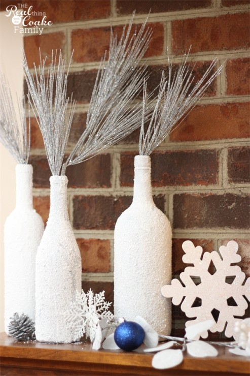 Pretty winter mantel decor using glitter snowflakes, wine bottles, candles and hurricane lamps. #Winter #Mantel #HomeDecor