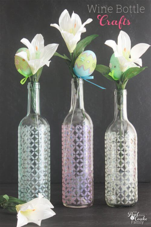 3 wine bottles made into vases with lily flowers in the vases