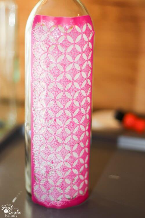 wine bottle with adhesive stencil on it covered with a layer of Mod Podge