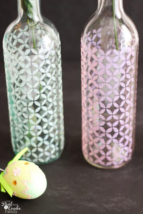 Showing 2 completed wine bottle crafts with glitter and stenciled pattern